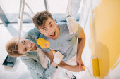 cheerful girl having fun while frightening boyfriend with paint roller