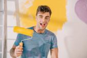 veselý mladý muž drží žlutou barvu váleček při pohledu na kameru