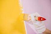 Teilansicht der Malerwand in gelb und rosa mit Pinsel