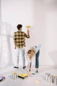 mladá žena uvedení barvy váleček do válečkové vaničky se žlutou barvou, zatímco přítel malování stěn