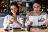woman smiling while using smartphone near man with menu