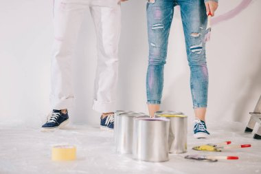 cropped view of man and woman standing by white wall near cans with paint