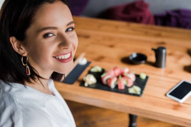 Selective focus of happy woman near smartphone with blank screen and tasty sushi in restaurant stock vector