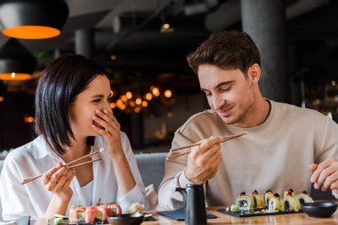 Happy man holding chopsticks near cheerful woman laughing while covering face in restaurant stock vector