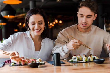 Selective focus of young man holding chopsticks near happy woman in sushi bar stock vector