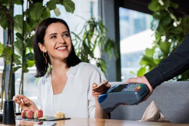 cropped view of waiter holding credit card reader near smiling woman paying with smartphone
