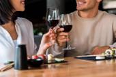 oříznutý pohled na šťastný muž a veselá žena cinkající sklenice s červeným vínem v blízkosti sushi