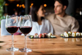 selective focus of glasses with red wine near happy man and woman