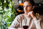 szelektív fókusz az ember ül az étteremben egy pohár vörösbor
