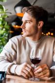 Selektiver Fokus eines gutaussehenden Mannes, der mit einem Glas Wein im Restaurant sitzt