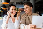 selektivní zaměření šťastný muž v blízkosti veselá žena mluví na smartphone