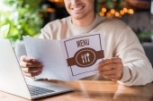 cropped view of happy man holding menu near laptop in restaurant