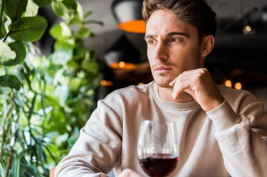 Selective focus of man sitting in restaurant with glass of red wine stock vector