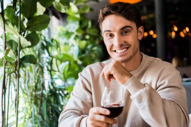 Happy man holding glass with red wine while looking at camera stock vector