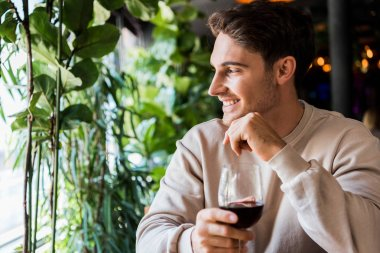 Happy man holding glass with red wine in restaurant stock vector