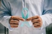 vista parziale del medico in cappotto bianco con nastro di consapevolezza blu
