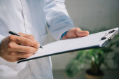 cropped view of doctor in white coat writing diagnosis on clipboard