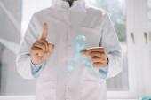 částečný pohled na lékaře držícího modrou informační stuhu a ukazujícího gesto pozornosti