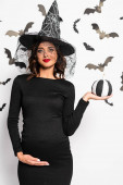 Photo pregnant woman in witch hat holding pumpkin in Halloween