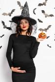 těhotná žena v klobouku čarodějnice drží dýně v halloween