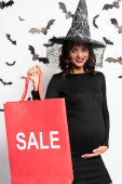 Photo pregnant woman in witch hat holding shopping bag with lettering sale in Halloween