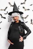 těhotná žena v čarodějnice klobouk a paruka při pohledu na kameru v halloween