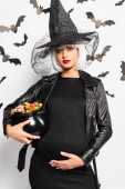 Photo pregnant woman in witch hat and wig holding pot with candies in Halloween