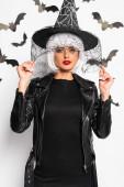 atraktivní žena v čarodějnice klobouk a paruka při pohledu na kameru v Halloween