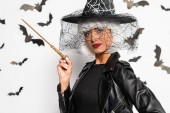 attractive woman in witch hat and wig holding magic wand in Halloween