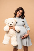 pregnant woman in grey dress holding teddy bear on beige background