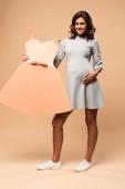 těhotná žena v šedých šatech drží papírové šaty na béžovém pozadí
