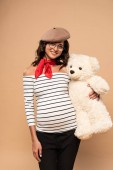 pregnant french woman in beret smiling and holding teddy bear on beige background