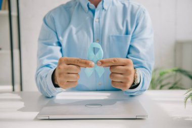 Cropped view of man in blue shirt holding blue awareness ribbon near laptop stock vector