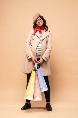 Pregnant french woman in coat holding shopping bags on beige background stock vector