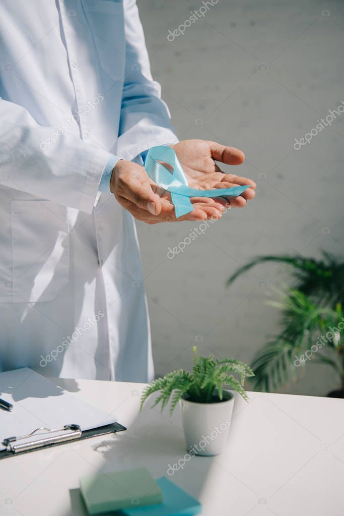 Cropped view of doctor holding blue awareness ribbon near table with clipboard and flowerpot stock vector