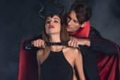 schöner Mann im Vampir-Halloween-Kostüm mit Peitsche in der Nähe einer Frau mit Hörnern auf schwarzem Rauch