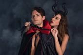 Fotografie attraktive Frau mit Hörnern und Peitsche in der Nähe eines Mannes im Vampir-Halloween-Kostüm auf schwarz mit Rauch