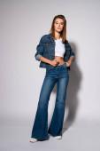 Fotografie stylisches Mädchen, das Jeans berührt, während es auf Weiß steht