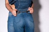 cropped view of man holding handcuffs near girl in jeans on white