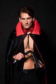 schöner Mann im Vampir-Halloween-Kostüm mit Prügelpeitsche isoliert auf schwarz