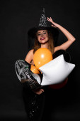Photo happy woman touching witch hat near balloons on black