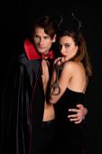 schöner Mann in Mantel umarmt Frau mit Hörnern hält Handschellen isoliert auf schwarz