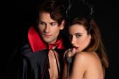 schöner Mann in Mantel in der Nähe einer Frau mit Hörnern, die Handschellen auf schwarz isoliert hält