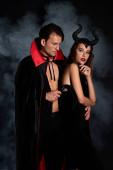 schöner Mann in Mantel mit Peitsche in der Nähe von Frau mit Hörnern auf schwarz mit Rauch
