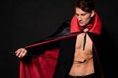 sexy Mann im Vampir-Halloween-Kostüm mit Prügelpeitsche isoliert auf schwarz