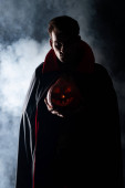 handsome man holding spooky pumpkin on black with smoke