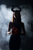 silhouette of woman with horns holding spooky pumpkin on black with smoke