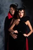 schöner Mann in Mantel umarmt Mädchen mit Hörnern hält Peitsche auf schwarz mit Rauch