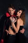 Fotografie dominante Frau mit Hörnern hält Handschellen in der Nähe von Mann im Mantel auf schwarz