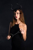 Fotografie attractive woman with horns holding handcuffs on black